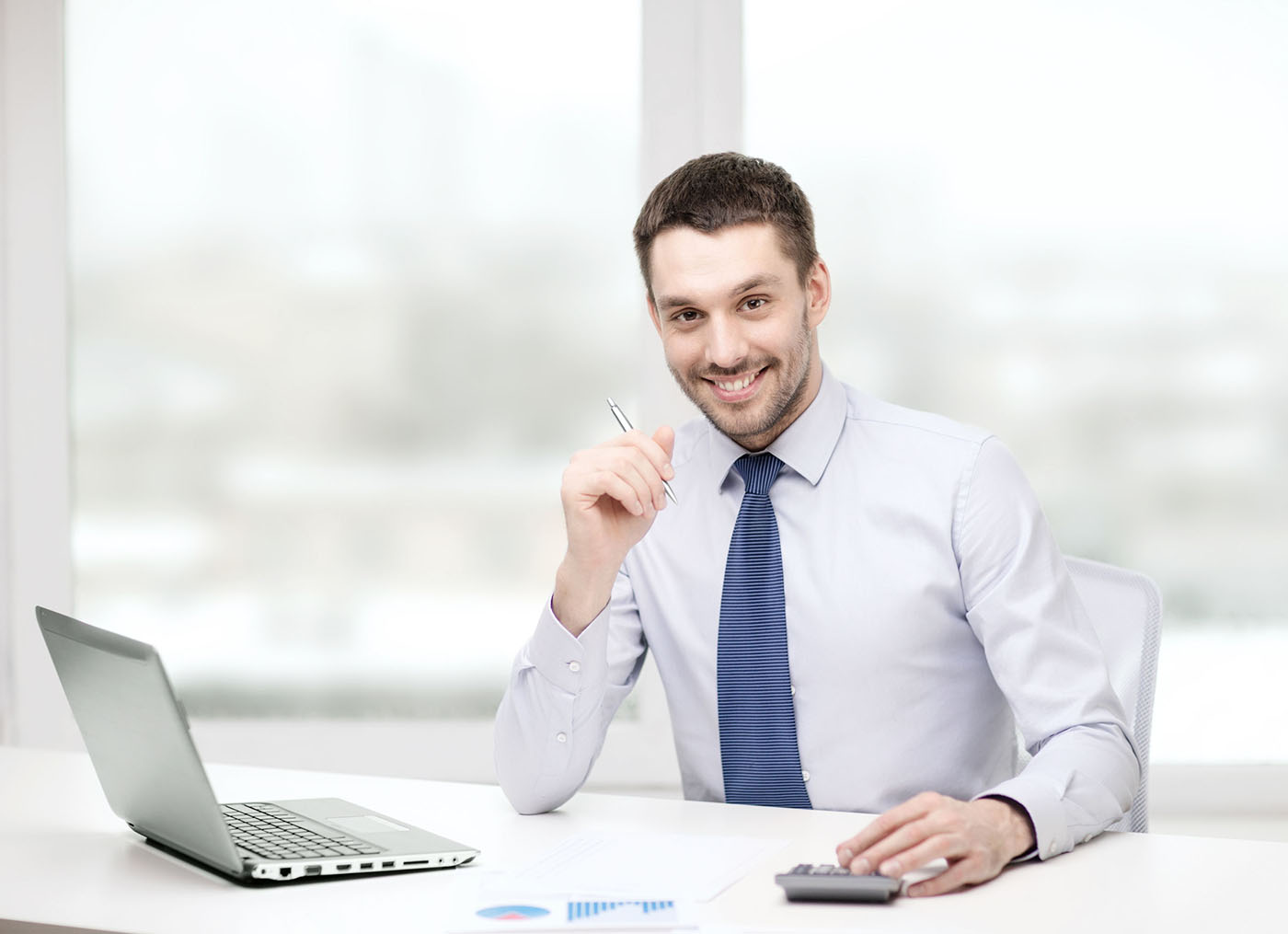 Man at computer with calculator